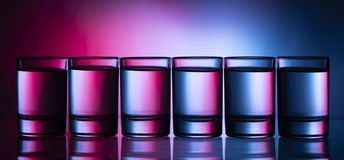 Six small multi-colored glasses on a bright background. Close up royalty free stock photos