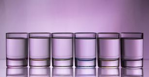 Six small multi-colored glasses on a bright background. Close up stock photo