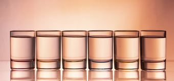 Six small multi-colored glasses on a bright background. Close up royalty free stock photography