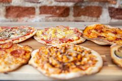 Six pizzas on a wooden board, fresh out of the oven with focus in hawaiian pizza stock photo