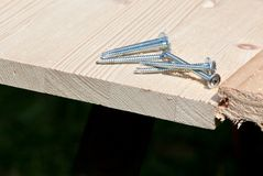 Six steel screws on wood plank Stock Photography