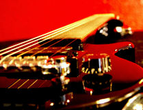 Six string. Black Guitar Red Background Stock Photography
