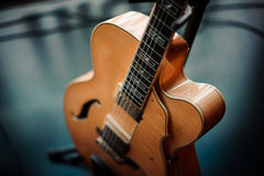Six-string acoustic guitar on a stand stock image