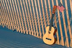 Guitar on beach fence with American flag. Six string guitar and American flag in beach sand on wooden fence Royalty Free Stock Image