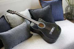 Six stringed acoustic guitar. On grey sofa Royalty Free Stock Image