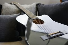 Six stringed acoustic guitar. On grey sofa Stock Images