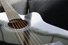 Six stringed acoustic guitar. On grey sofa Royalty Free Stock Photo