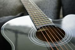 Six stringed acoustic guitar. On grey sofa Stock Photography