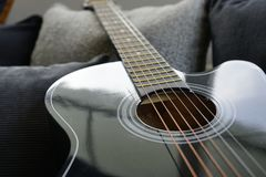 Six stringed acoustic guitar. On grey sofa Stock Photo