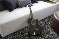Six stringed acoustic guitar. On grey sofa Royalty Free Stock Photography