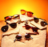 Six sunglasses over sand and stones. Beach decoration. Fashion accessories Royalty Free Stock Photography