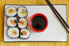 Six sushi rolls with soy sauce and chopsticks. A view from above on a composition of six sushi rolls with a small bowl of soy sauce and chopsticks with some room Royalty Free Stock Images