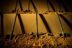 Six symmetrically placed shovels stuck into the ground stock photo
