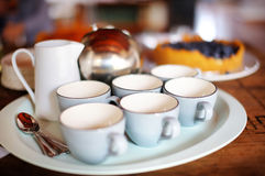 Six tea cups and a teapot Stock Images