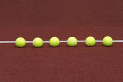 Six tennis balls in-line on court Royalty Free Stock Photo