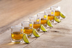 Six tequila shots in a row with lime slice and salt Stock Photography