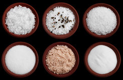 Six terracotta plates with sea salt on black Stock Photo