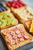 Six toasts with peanut butter, fresh fruits on a grey slate stock photos