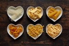 Six types de pâtes crues dans des cuvettes en forme de coeur Images stock