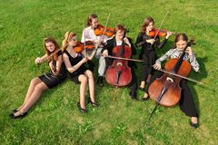 Six violinists sit semicircle on  grass and play. Six violinists sit semicircle on green grass and play Royalty Free Stock Image