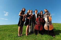 Six violinists stand on grass against sky. Six violinists stand on green grass against sky, wide angle Royalty Free Stock Photo