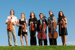Six violinists stand on  grass against sky. Six violinists stand on green grass against sky Royalty Free Stock Images