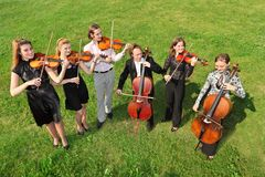 Six violinists stand semicircle on  grass and play. Six violinists stand semicircle on green grass and play Royalty Free Stock Photo