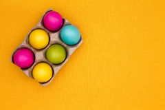 Six vivid colored Easter eggs in a carton. High-angle close-up of six vivid colored Easter eggs in a carton, on a table covered by a yellow cotton tablecloth Stock Photo