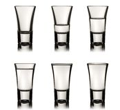 Six vodka glasses. With various level of liquid, clipping path is included Stock Photo