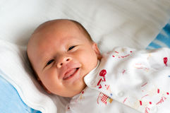 Six week baby with tongue. Six week baby lying on diaper. Baby is smiling straight at camera with tongue Stock Image