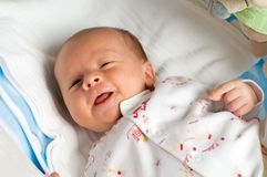 Six week baby with tongue. Six week baby lying on diaper. Baby is smiling straight at camera with tongue Stock Photo