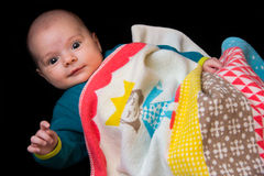 Six week old baby lying covered in blanket  on black Stock Photos