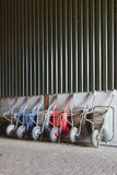 Six wheelbarrows rest against wall of farm barn stock images