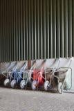 Six wheelbarrows rest against wall of farm barn Stock Images