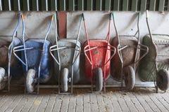 Six wheelbarrows rest against wall of farm barn Stock Image