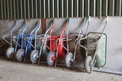 Six wheelbarrows rest against wall of farm barn Stock Photography