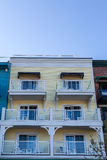 Six White Balconies on Yellow Wood Building Stock Images