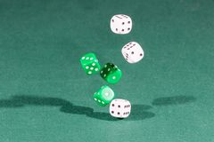 Six white and green dices falling on a green table. Six white and green dices falling on a isolated green table royalty free stock image