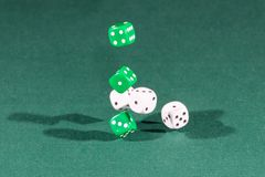 Six white and green dices falling on a green table. Six white and green dices falling on a isolated green table royalty free stock photo
