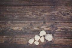 Six white rocks on wooden deck.  stock photo