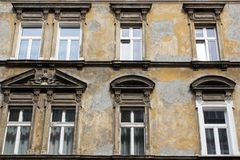 Six windows on the facade of the ragged old house.  Royalty Free Stock Image
