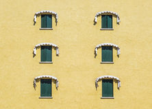 Six Windows with Green Shutters on yellow wall of old italian House, Italy Royalty Free Stock Photo