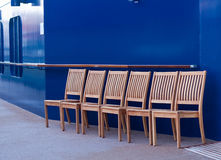 Six Wood Chairs on Ships Deck by Blue Wall Royalty Free Stock Images
