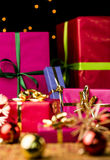 Six Wrapped Christmas Gift Boxes. Presents packed in plain papers for Christmas. Narrow depth of field. Focus is on the small magenta gift box with the golden Stock Photos