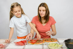 Six-year girl helps mother Stock Image