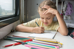 Six-year girl joyfully draws pencils in second-class train carriage Stock Photo