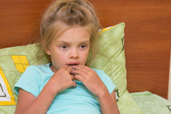 Six-year girl looks thoughtfully at one point and keeps finger mouth. Six-year girl looks thoughtfully at one point and keeps finger in mouth royalty free stock photo