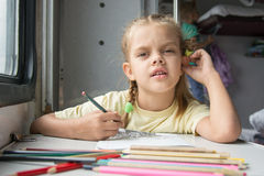 A six-year girl in the picture looked drawing pencils in a second-class train carriag Stock Photos