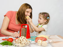 Six-year girl with pigtails giving mom bite out of a piece of cheese at the kitchen table where they cook together Stock Photography