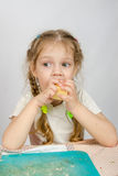 Six-year girl with pigtails trying to bite off piece of cheese that keeps both hands Royalty Free Stock Photo
